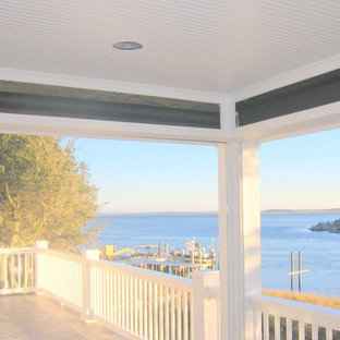 Design ideas for a large beach style backyard deck in Other with a roof extension.