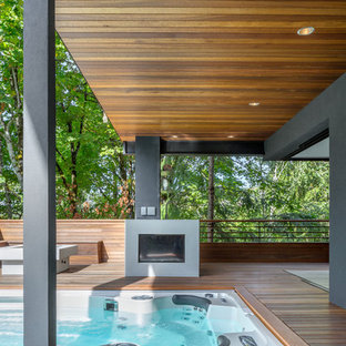 Inspiration for a contemporary deck remodel in Portland with a fire pit and a roof extension