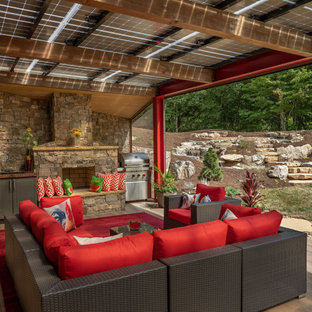 Example of a large trendy backyard deck design in Other with a fireplace and a pergola