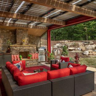 Ispirazione per una grande terrazza minimal dietro casa con un caminetto e una pergola