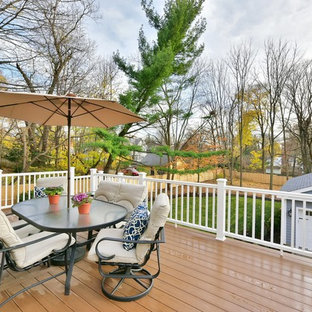 Example of a large ornate backyard deck design in New York with a roof extension