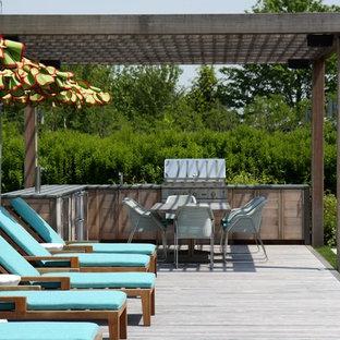 Esempio di una terrazza country con una pergola