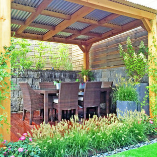 Example of a trendy backyard deck container garden design in New York with a pergola