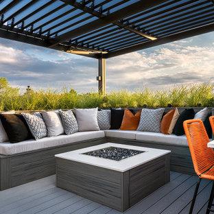 Immagine di un'ampia terrazza minimalista sul tetto con un caminetto e una pergola