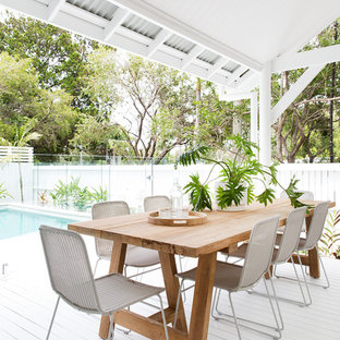 This is an example of a beach style deck in Brisbane with a roof extension.