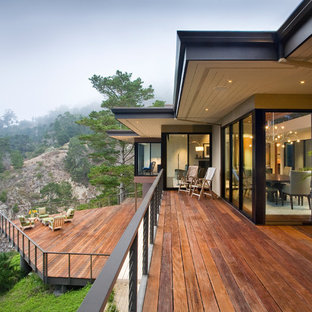 Inspiration for a huge contemporary backyard deck remodel in Other with a roof extension