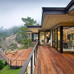 Inspiration för mycket stora moderna terrasser på baksidan av huset, med takförlängning