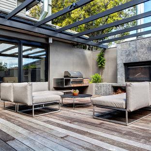 Immagine di una terrazza design dietro casa con una pergola e un focolare