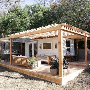 Deck - small shabby-chic style backyard deck idea in Austin with a pergola