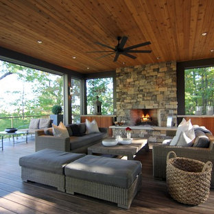 Inspiration for a large contemporary backyard deck remodel in Raleigh with a fire pit and a roof extension