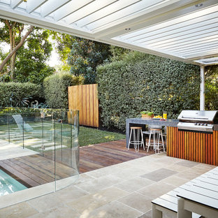 This is an example of a contemporary backyard deck in Sydney with a pergola.