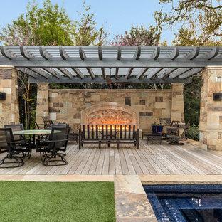 Foto på en medelhavsstil terrass på baksidan av huset, med en öppen spis och en pergola