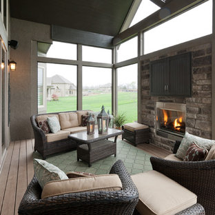 Example of a mid-sized transitional backyard deck design in Kansas City with a fire pit and a roof extension