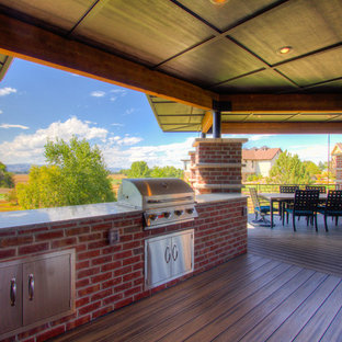 Photo of a large vintage back terrace and balcony in Denver with an outdoor kitchen and a roof extension.