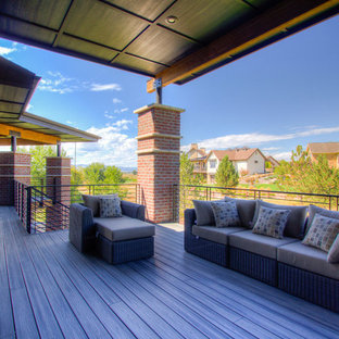 Example of a large cottage chic backyard deck design in Denver with a roof extension
