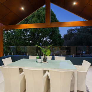 This is an example of a beach style deck in Perth with a roof extension.