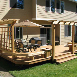 Inspiration for a large modern backyard outdoor kitchen deck remodel in Seattle with a pergola