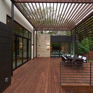 Ispirazione per una grande terrazza minimal dietro casa con una pergola