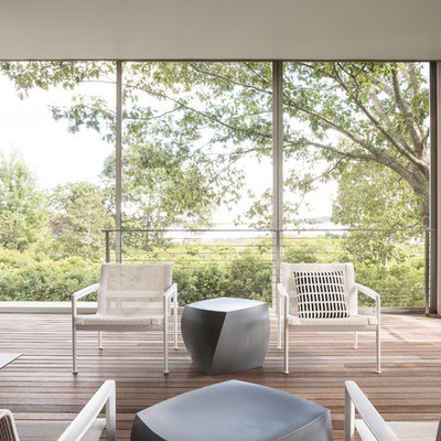 Example of a trendy deck design in Portland Maine with a fire pit and a roof extension