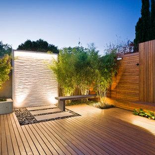 Imagen de terraza contemporánea, sin cubierta, en patio trasero, con fuente