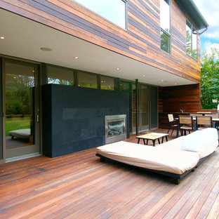 Example of a mid-sized trendy backyard deck design in Seattle with a fire pit and no cover