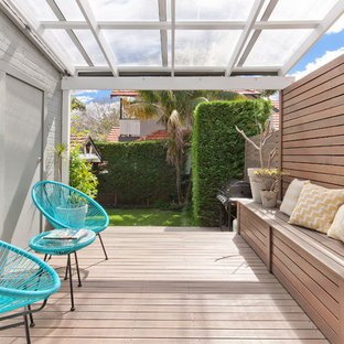 Deck - mid-sized scandinavian backyard deck idea in Other with a pergola