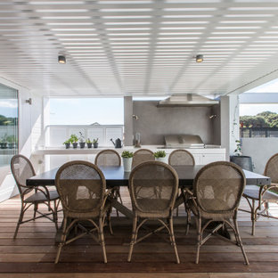 Large beach style backyard deck in Perth with an outdoor kitchen and a roof extension.