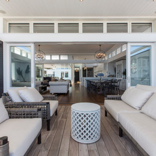 Design ideas for a mid-sized beach style backyard deck in Perth with a roof extension.