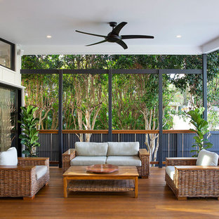 Mid-sized beach style backyard deck in Brisbane with a roof extension.