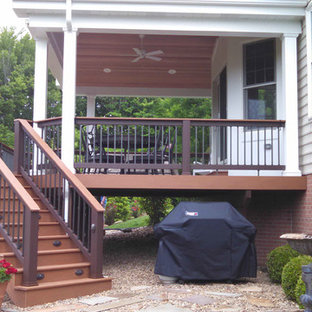 Example of a mid-sized classic backyard deck design in Other with a roof extension