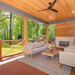 Example of a farmhouse backyard deck design in Charlotte with a fireplace and a roof extension