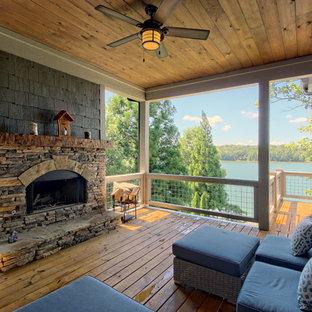 Ispirazione per terrazze e balconi american style di medie dimensioni e dietro casa con un caminetto e un tetto a sbalzo