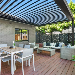 Photo of a large contemporary backyard deck in Sydney with a pergola.