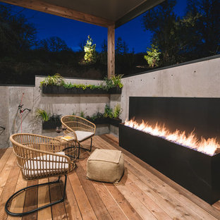 Deck - rustic deck idea in Portland with a roof extension and a fireplace