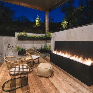 Idee per una terrazza rustica con un tetto a sbalzo e un caminetto