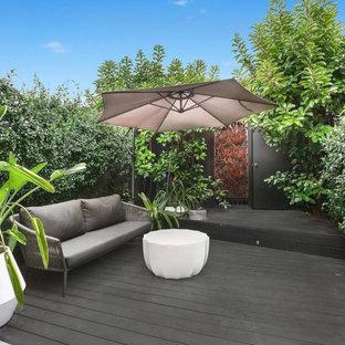 Foto på en mellanstor 50 tals terrass på baksidan av huset, med en vertikal trädgård och takförlängning