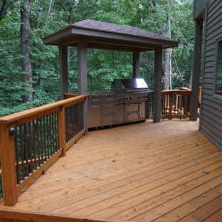 Huge mountain style backyard outdoor kitchen deck photo in Chicago with an awning