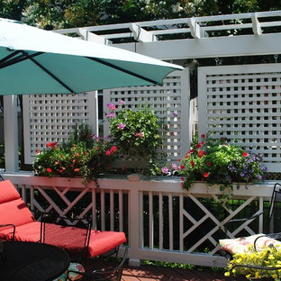 Example of an eclectic backyard deck design in Other