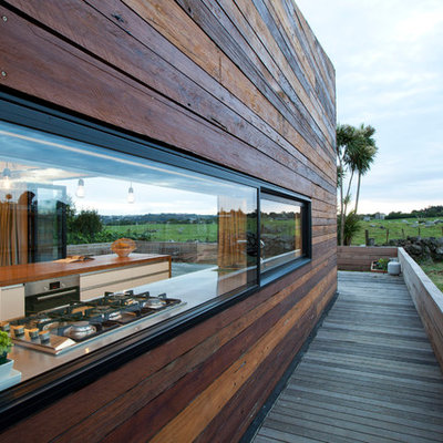 Example of a small trendy side yard deck design in Auckland with no cover