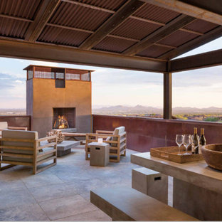Inspiration for a southwestern deck remodel in Phoenix with a fire pit and a roof extension