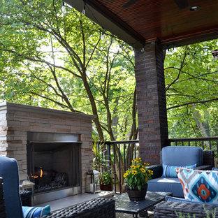 Modelo de terraza clásica renovada, de tamaño medio, en patio trasero y anexo de casas, con chimenea