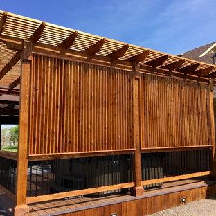 Inspiration pour une terrasse arrière traditionnelle de taille moyenne avec une pergola.