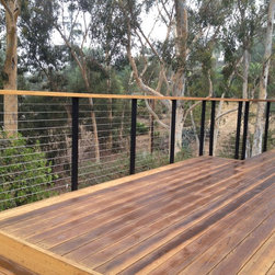 Deck Cable Railing - Steel Cable Railing Kit installed by the owner of this beautiful mountain home. Black railing posts provide contrast with redwood decking, and stainless steel cable infill provides a safe and transparent barrier for safety on this raised hillside deck.