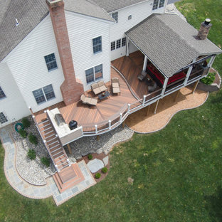 Example of a large classic backyard deck design in Baltimore with a fire pit and a roof extension