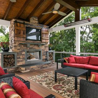 Cette image montre une grande terrasse arrière traditionnelle avec une extension de toiture.