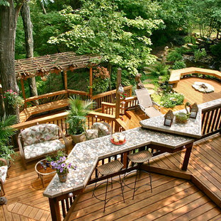 Design ideas for an expansive traditional backyard deck in Other with a pergola and a fire feature.