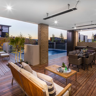 Contemporary backyard deck in Canberra - Queanbeyan with an outdoor kitchen and a roof extension.