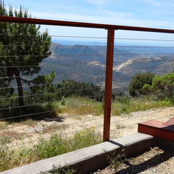 Cable Railing Kits - Invisible barrier railing constructed for a palomar mountain view home. Galvanized steel post system combined with stainless steel cable and a mangaris hardwood top railings. Connections were made to the deck and existing masonry wall.