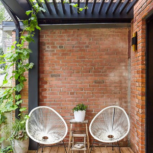 Deck container garden - small scandinavian backyard deck container garden idea in Toronto with a pergola
