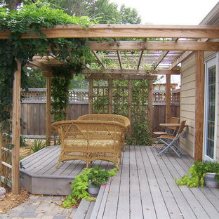 Design ideas for a small country backyard deck in Minneapolis with a pergola.